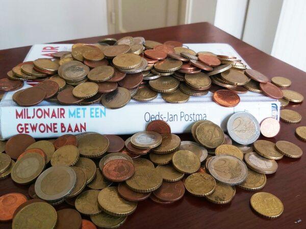Boek Miljonair met een gewone baan met kleingeld erop